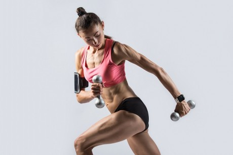Portrait of beautiful young fitness person wearing smartwatch, smartphone armband, red sportswear top working out. Sporty model doing Standing Single Arm Dumbbell Row with dumbbells in lunge position